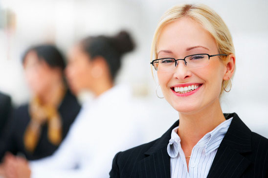 Blonde office woman with glasses smiling with office co workers in background