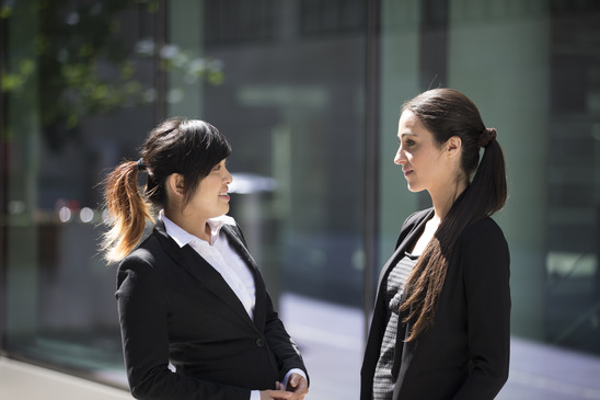 Two Happy Business women outside the office talking to each other.
