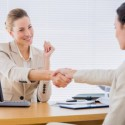 Smartly dressed young women shaking hands in a business meeting at office desk featured