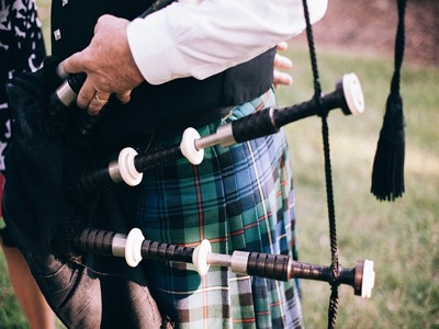 man playing bagpipes in kilt burn's night featured