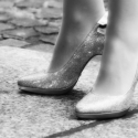 Standing on your own two heels - A grayscale picture of two high heels with a woman standing in them.
