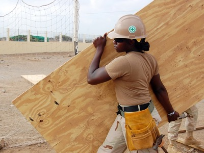 female apprentice construction worker carrying plank of wood featured