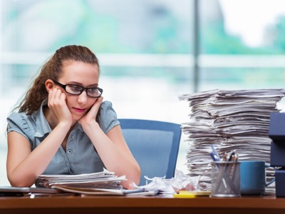 Woman looking miserably at her pile of work