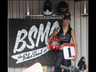 Vikki holding a red helmet, smiling outside a sign for the bike shed