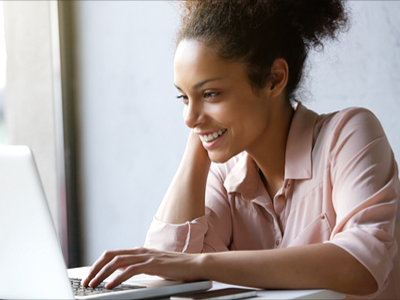 Young, smiling woman smiling whilst on her laptop