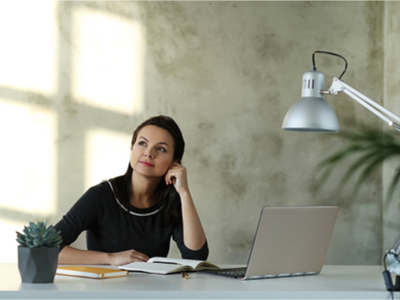 woman thinking at her desk with computer