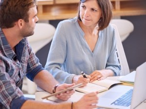 confident woman mentoring male colleague featured