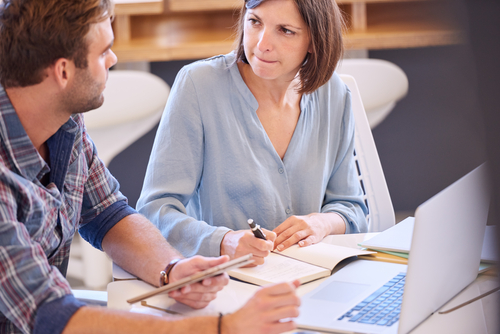 confident woman mentoring male colleague