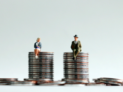 man and woman sitting on pile of coins, Equal Pay Day