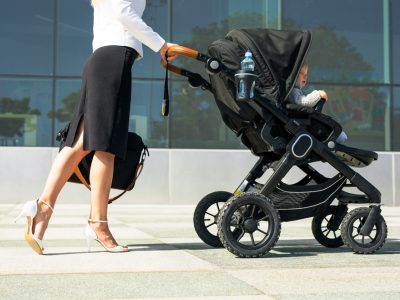 Business mother pushing baby on the way to work, working mum