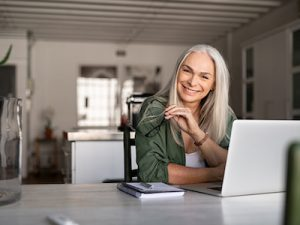 Portrait of happy senior woman holding eyeglasses and looking at camera at home. Successful old lady laughing and working at home, menopause