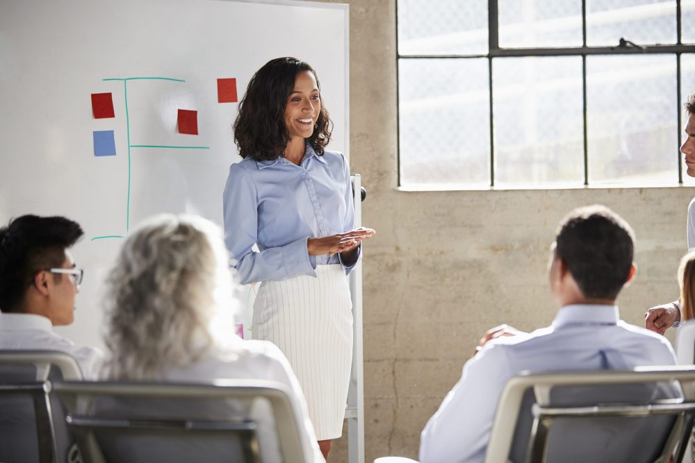 Mixed race businesswoman giving a presentation at a meeting