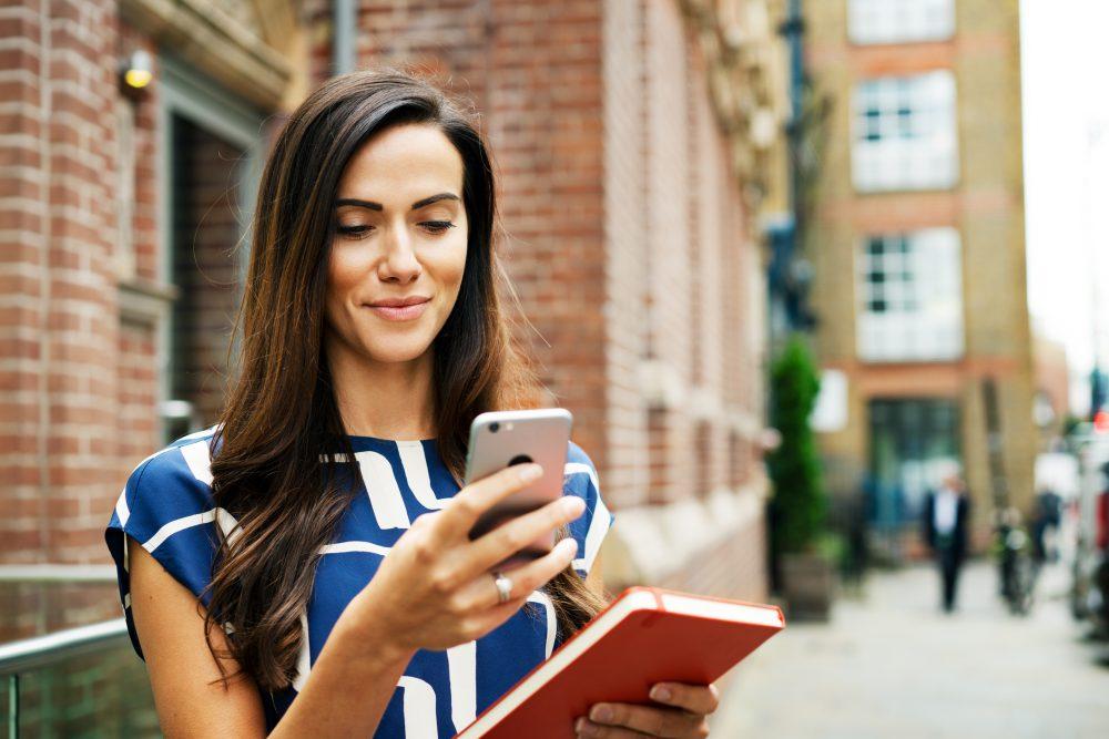 Woman using smart phone on street