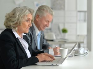 Older business man and woman on laptop, supporting older workers