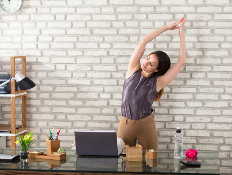 woman stretching in the office, office exercise, workout, working from home during coronavirus