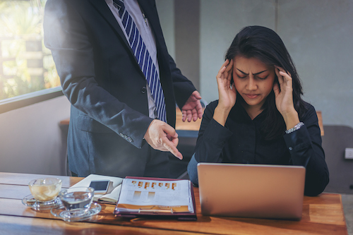 Toxic boss blaming woman for her work in the office. Woman has a headache, hyper masculinity