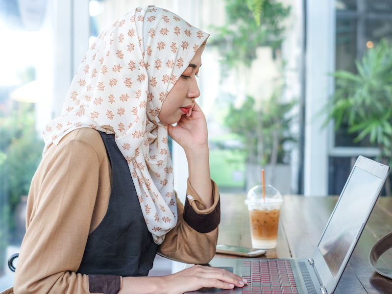 Young Thai Melayu female freelancer wearing hijab work using a laptop on wooden table in coffee shop. Modern woman life style.