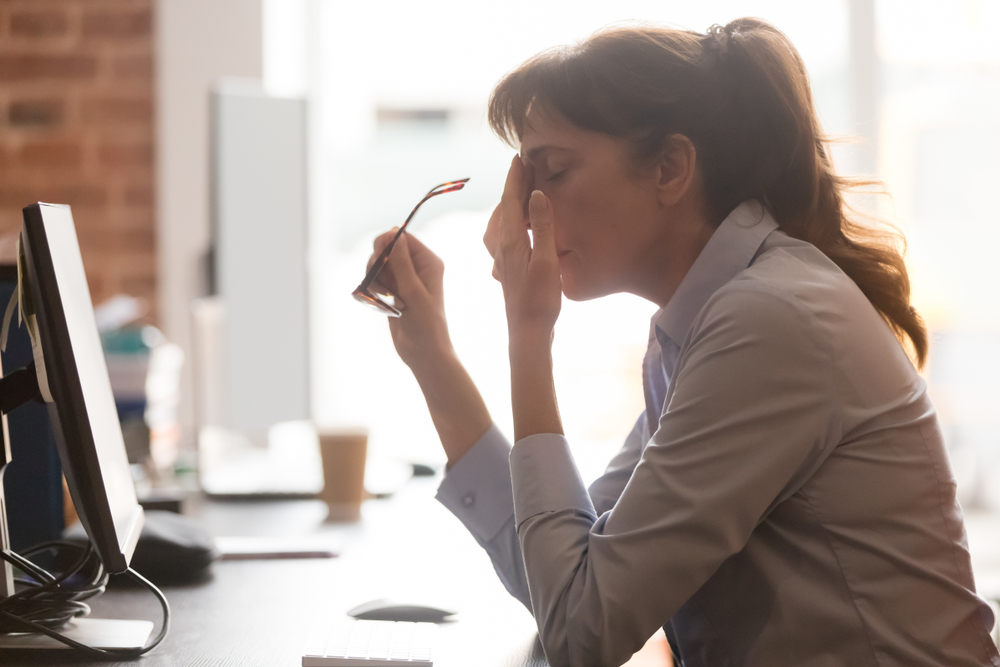 Exhausted female worker sit at office desk take off glasses feel unwell having dizziness or blurry vision, tired woman employee suffer from migraine or headache unable to work. Health problem concept, employees