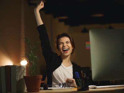 Picture of yawning young woman designer sitting in office at night using computer.