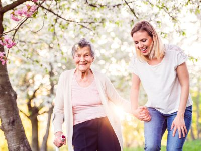 Elderly grandmother with crutch and granddaughter in spring nature, carer