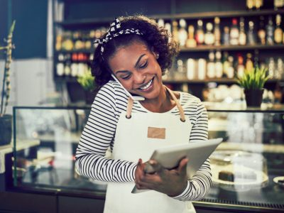 Smiling young African entrepreneur standing in front of the counter of her cafe talking on a cellphone and using a tablet, single parent business owner