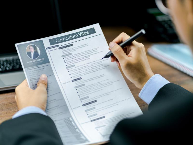 man looking at a CV, curriculum vitae, resume