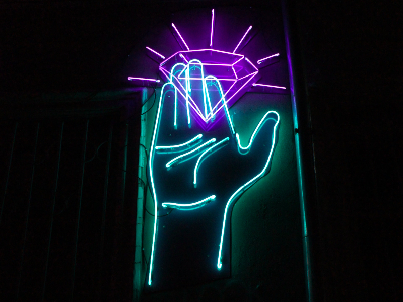 neon sign, hand holding a diamond