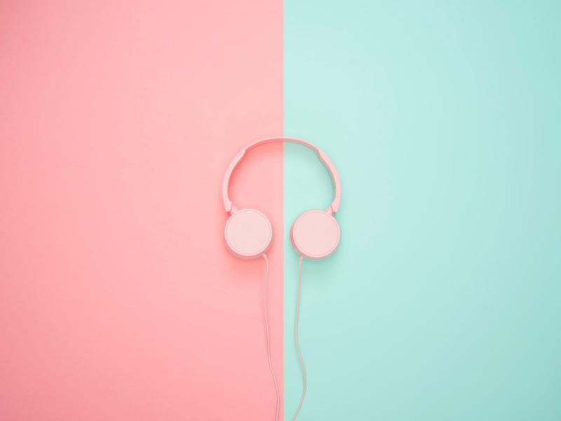 pink headphones on background, wearing headphones at work