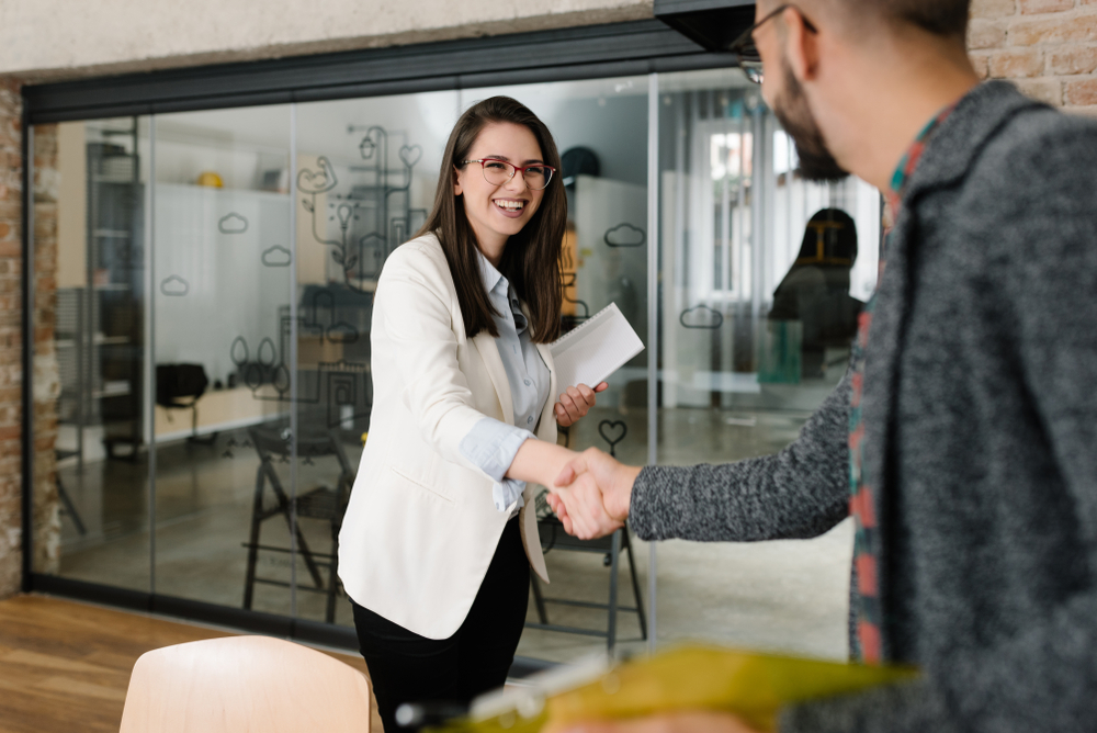 Openly greeting a job recruiter with a firm handshake, recruitment industry