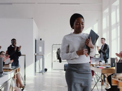 shy, introverted woman being clapped in the office
