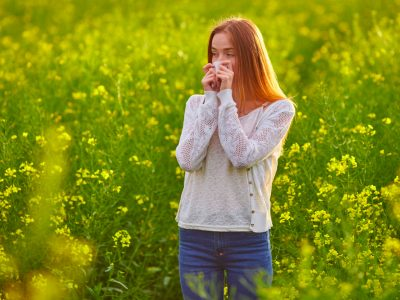 woman with hayfever standing in a field of flowers, allergies