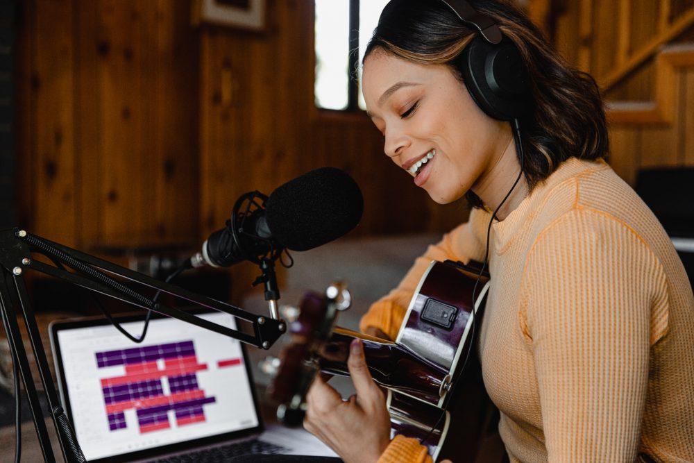 black woman playing guitar, music studio, music industry