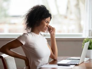 Tired african American millennial female worker sit at desk touch back suffer from lower spinal spasm, working from home