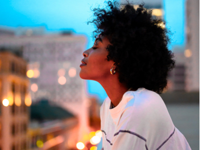 black woman looking out from balcony, wellbeing
