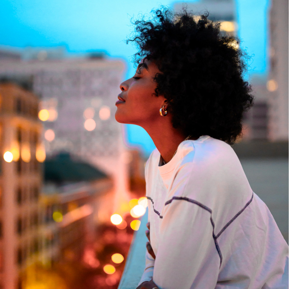 black woman looking out over balcony, wellbeing, relax