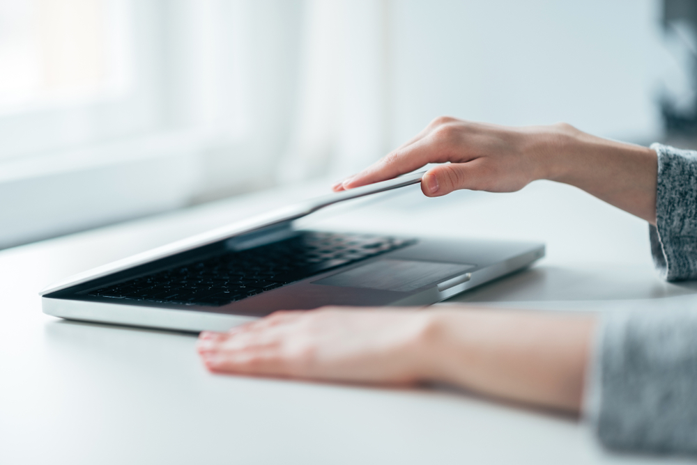 Close-up image of female hands open or close laptop on white table, work-life balance, working from home