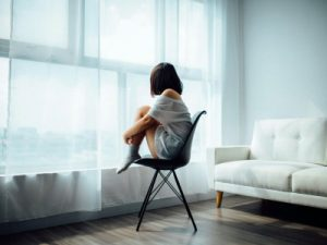 woman sat on a chair in the middle of the room, anxierty, mental health