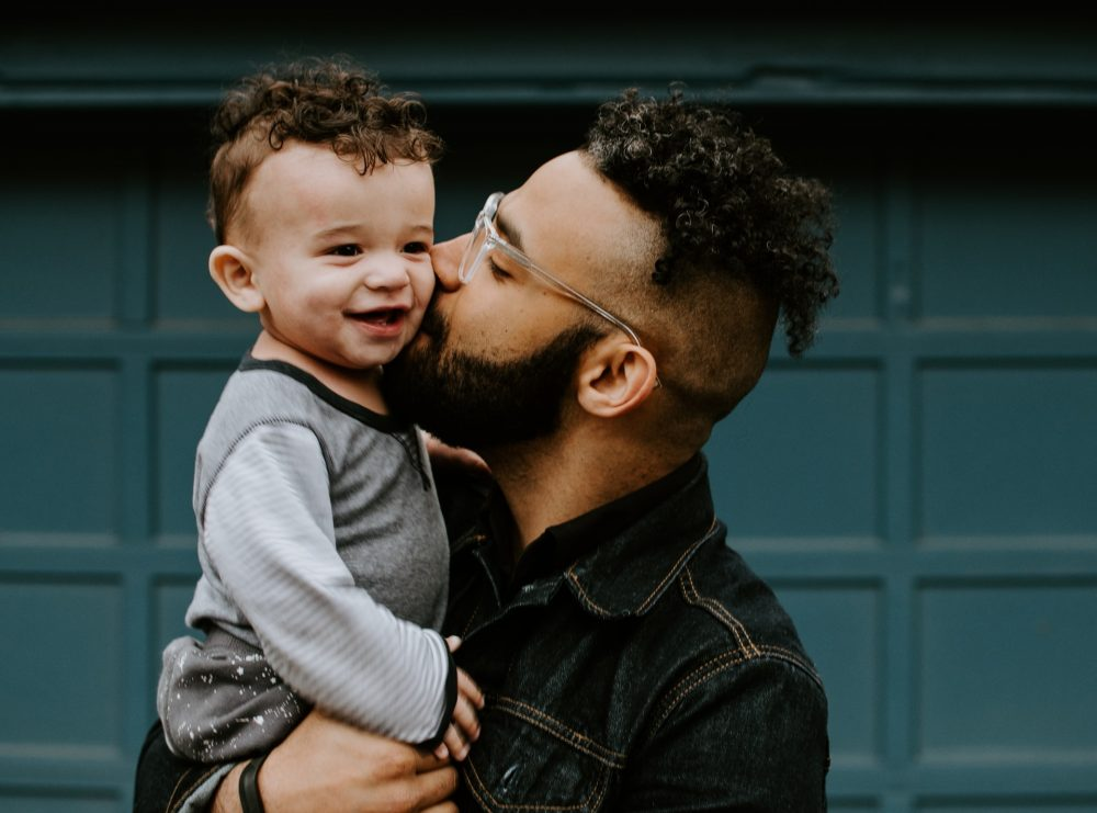 Dad carrying and kissing his son, parenting
