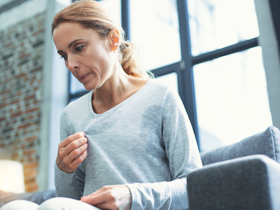 menopause, mature woman touching sweater and having hot flash