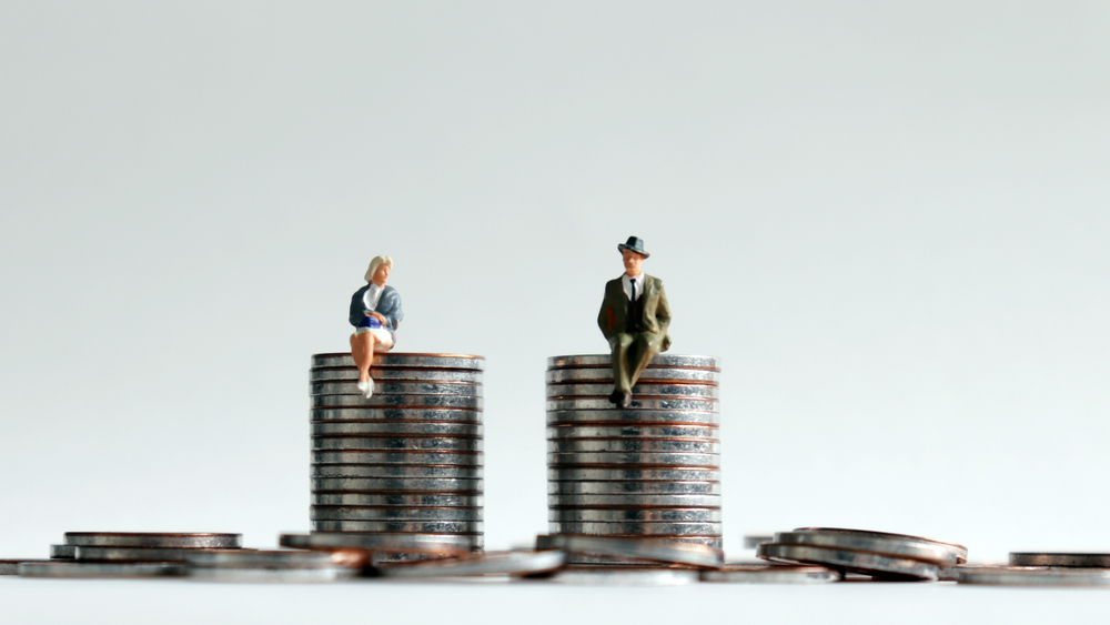 Equal Pay Day concept, man and woman sitting on a pile of money