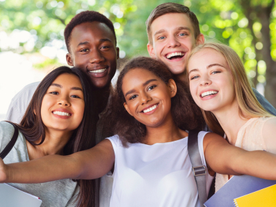 Cheerful international friends teenagers taking selfie while walking in summer park, young generation