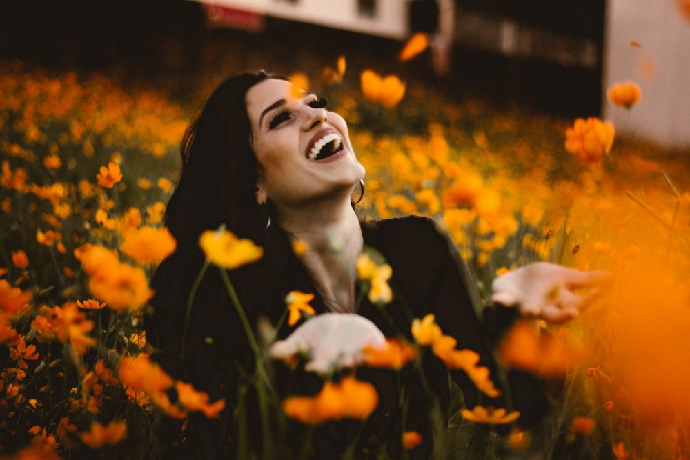 woman smiling in a field of flowers, growth, grow