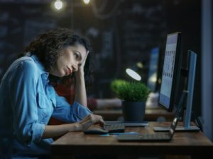 Tired, Overworked Female Financier Holds Her Head in Hands while Working on a Personal Computer