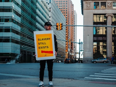 man holding a sign in the street, saying slavery still exists
