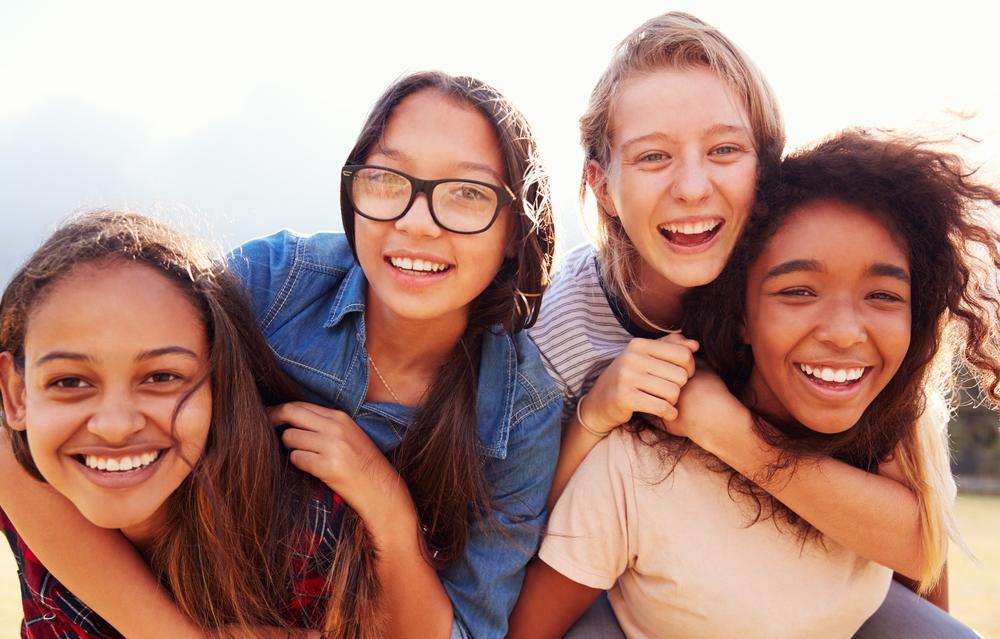 Four teenage girls having fun piggybacking outdoors, Reach Next Generation summit, empowerment