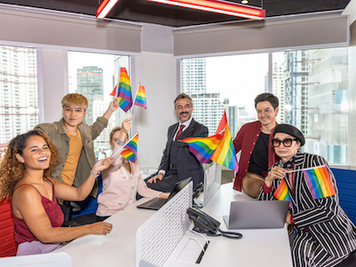 Business office workers from different ethnicities express support for self determination in LGBT. Business people showing LGBT flags in an office. Business people support Gender Equality