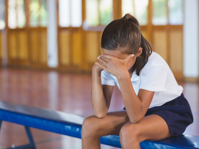 Sad schoolgirl sitting alone in basketball court at school gym, sexual harassment in school