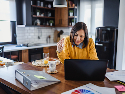 Young business entrepreneur woman working at home while having breakfast, World Productivity Day