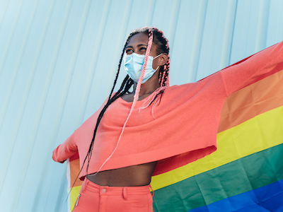 young gay black woman holding pride banner, LGBTQ