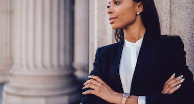 Female African American banker dressed in elegant black suit folding hands and looking on side standing against office building.